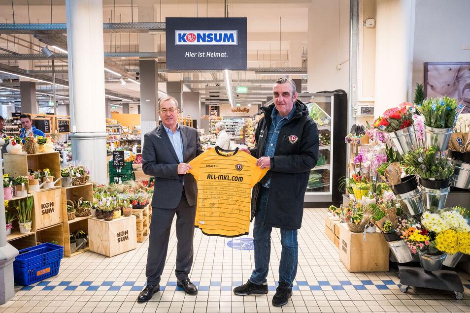 Dynamos Sport-Geschäftsführer Ralf Minge (r.) zeigt gemeinsam mit Vorstandssprecher Roger Ulke vom Konsum eines der 200 Trikots.
