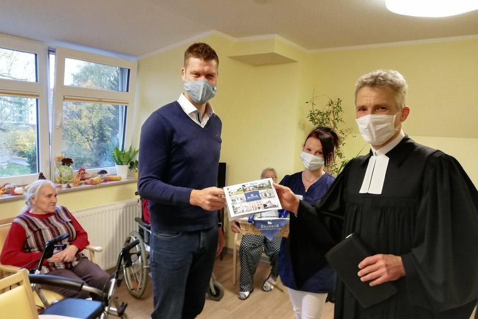 Benjamin Brambor (links) vom gleichnamigen Pflegedienst und Teamleiterin Sina Schumann überreichten an den Waldheimer Pfarrer Reinald Richber eine Spende. Im Anschluss hielt der Pfarrer einen Gottesdienst ab.
