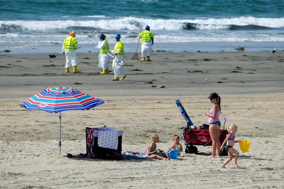 Besucher, die nicht ins Wasser dürfen, spielen am Strand während Arbeiter in Schutzanzügen den verunreinigten Sand nach einer Ölpest in Newport Beach, Kalifornien, abtragen.