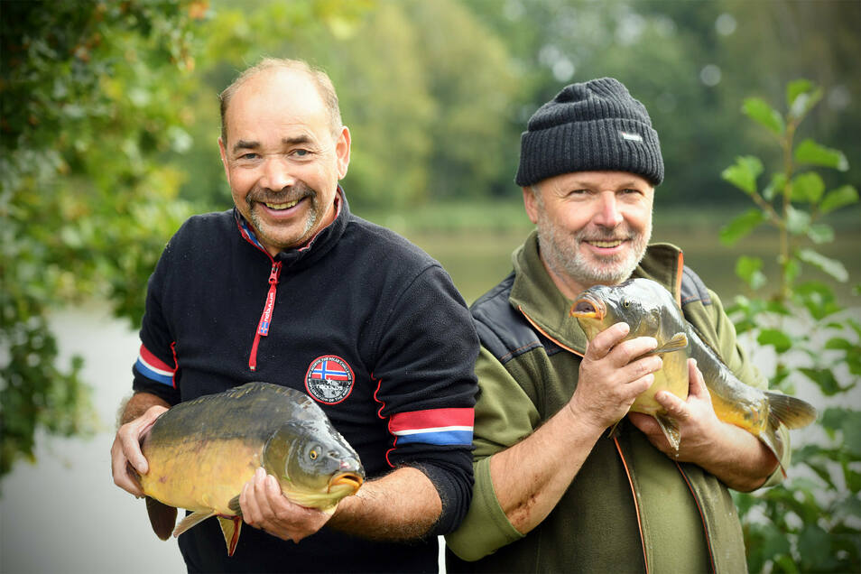 Hagen Dutschke (rechts) und Wolfgang Kahlert zeigen stolz, wie groß die Karpfen in diesem Jahr am Leubner Teich in Großhennersdorf geworden sind.