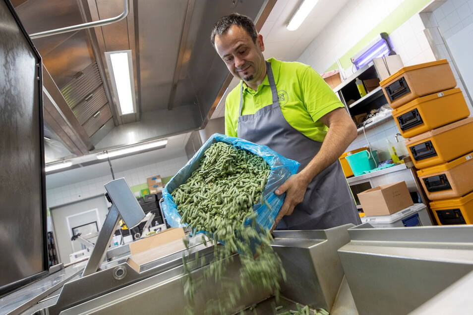 """Über 3.000 Portionen täglich: """"Knack Frisch""""-Küchenleiter Nino Stagge schüttet am neuen Arbeitsplatz Bohnen in einen Kochbehälter."""