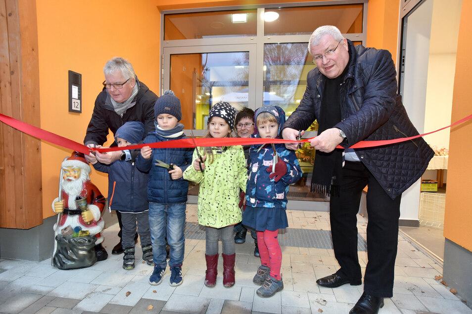 Geschafft: mit dem traditionellen Durchschneiden des Bandes haben die Kinder ihre neue Kita eröffnet. Landrat Bernd Lange (links) und Staatssekretär Herbert Wolff halfen.