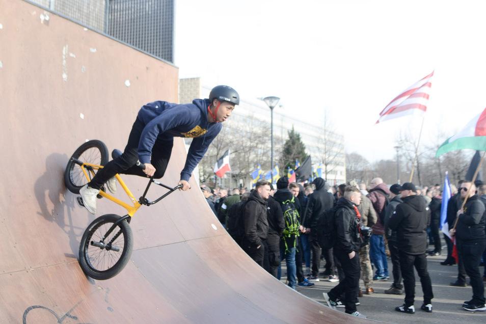 Ein junger Fahrradfahrer übt neben der Neonazi-Demo seine Tricks.