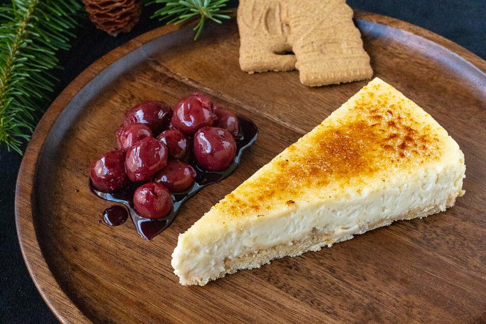 Weihnachtskuchen auf der Basis von New York Cheesecake zubereitet und mit Kirschen serviert.