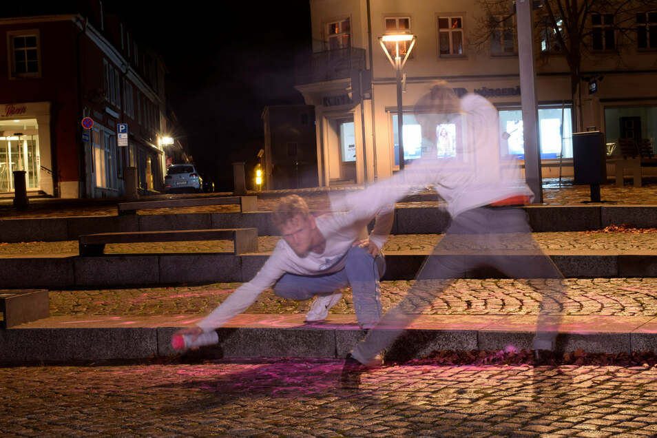 """Sie tanzt, er sprüht. Jana Schmück und Patrick von Bardeleben haben am Sonntagabend die Aktion """"Invisible Dances"""" auf dem Altmarkt in Bischofswerda und vor dem ehemaligen Kino umgesetzt."""