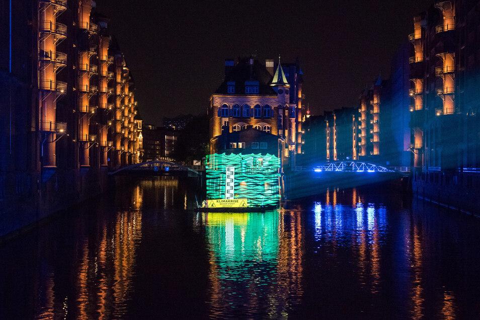 Greenpeace-Aktivisten projizieren in Hamburg die mögliche Höhe des Wasserstands zum Ende des Jahrhunderts auf das Wasserschloss.