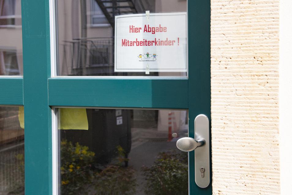 Nicht zu verfehlen: Ein Schild an der Haustür des Nebengebäudes weist darauf hin, dass hier die Kinder der Mitarbeiter betreut werden.