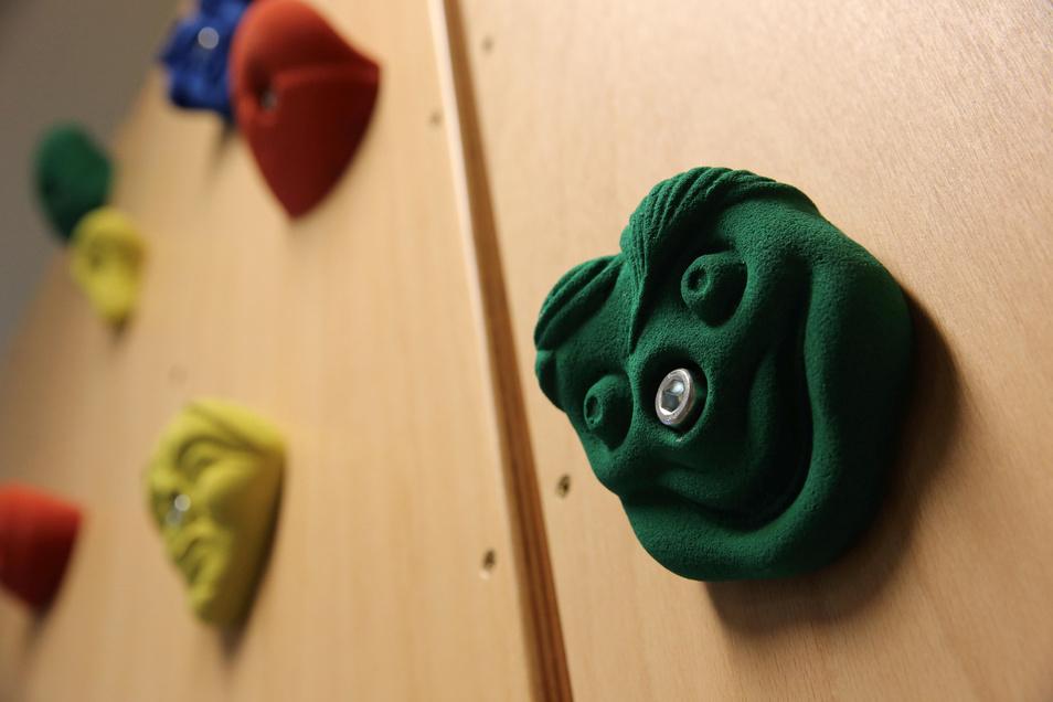 Im Sportsaal haben die Klettergriffe lustige Gesichter. Aber die Kinder sollen sich davon nicht ablenken lassen, sondern konzentriert nach oben steigen.