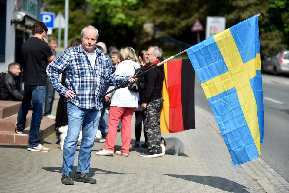 Dieser Mann hält die Schwedenfahne in der Hand, weil Deutschland sich seiner Meinung nach an dem Land ein Beispiel nehmen könnte.