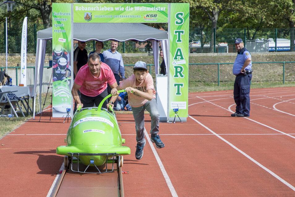 Torsten Engel schiebt mit seinem Sohn Ben Petermann einen Bob an auf der Sport- und Erlebnismeile im Stadion des Friedens im Rahmen des Windbergfestes Freital.