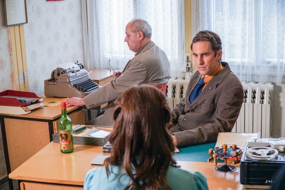 Eine junge Frau sitzt in einer nachgestellten Szene in einem Verhör mit zwei Mitarbeitern der Staatssicherheit.