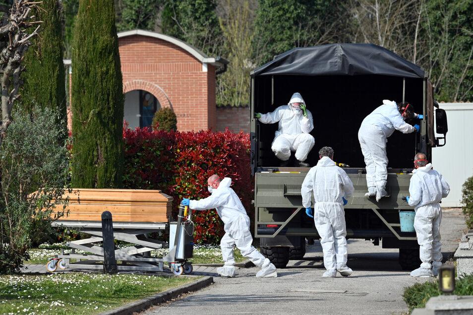 Menschen in Schutzanzügen transportieren einen Sarg mit einer Leiche des Verstorbenen aufgrund des Coronavirus auf dem Friedhof von Ferrara. Italien hat im ganzen Land eine Ausgangssperre verhängt, die am Freitag noch mal verschärft wurde.