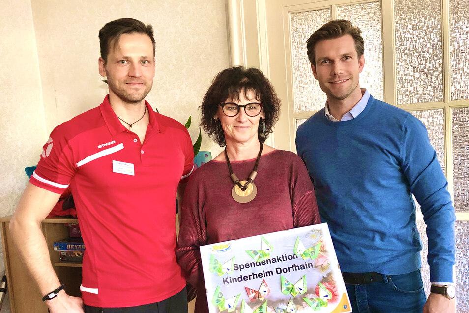 Sybille Clemens, Leiterin des Kinderheims Dorfhain nimmt die Spende von Frank Eytner (links), Leiter des Fitnessclubs und Daniel Wirth, Leiter des Freizeitzentrums Hains entgegen.