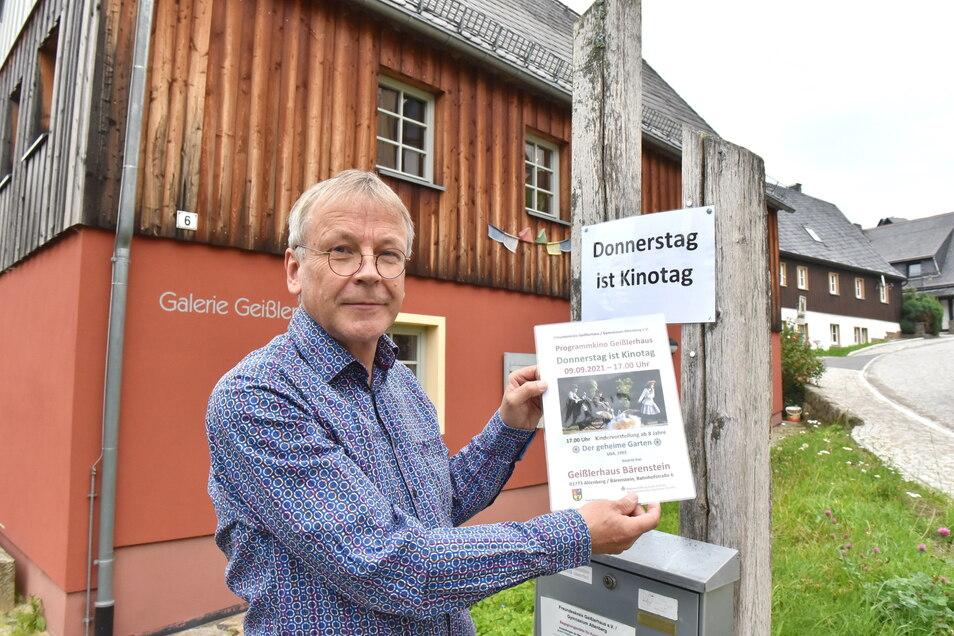 Karsten Franz bringt am Bärensteiner Geislerhaus das Werbeplakat für die nächste Studiokino-Vorführung an.