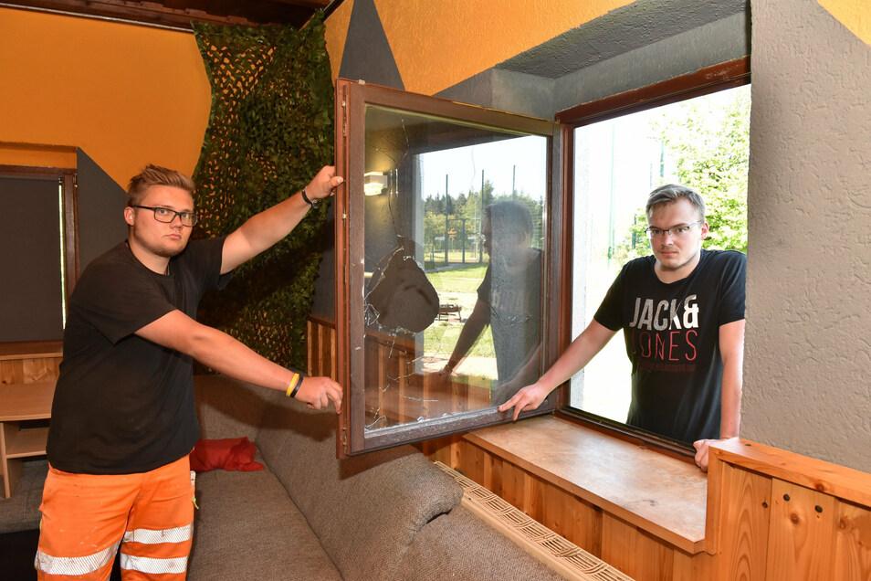 Florian Hermus und Max Tändler (re.) vom Vorstand stehen am eingeschlagenen Fenster über das der oder die Täter eingestiegen sind.