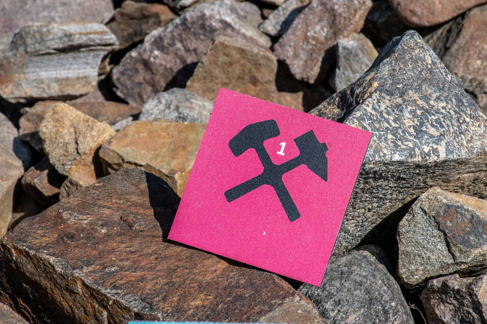 Schlägel und Bergeisen - beide Werkzeuge gekreuzt, stellen das traditionelle Symbol für den Bergbau dar. Am Lehrpfad finden sie Wanderer von knalligem Pink und Türkis umgeben.