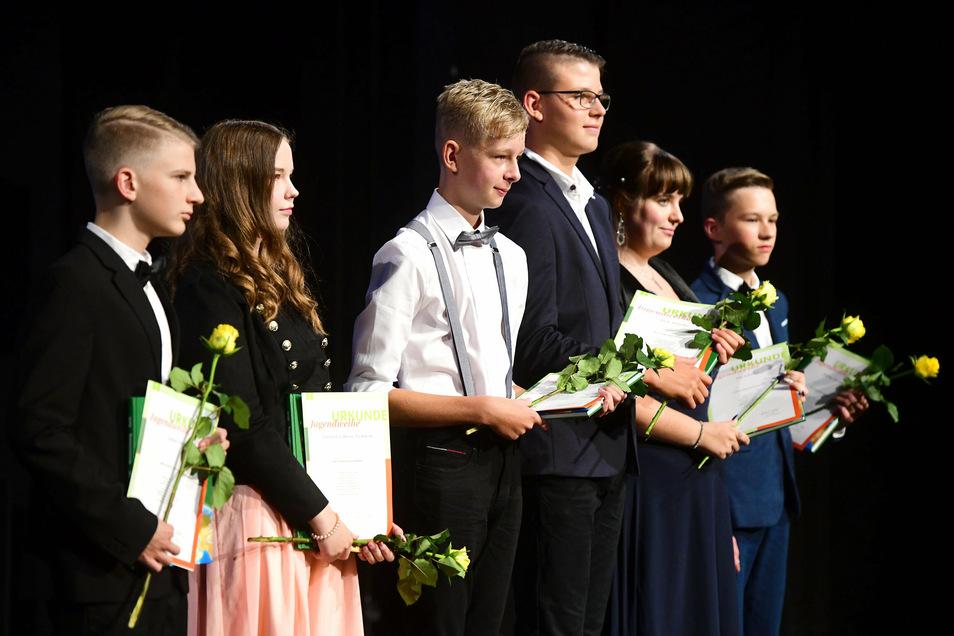Teilnehmer der Jugendweihe mit dem Geschenkbuch und einer gelben Rose auf der Bühne des Theaters.