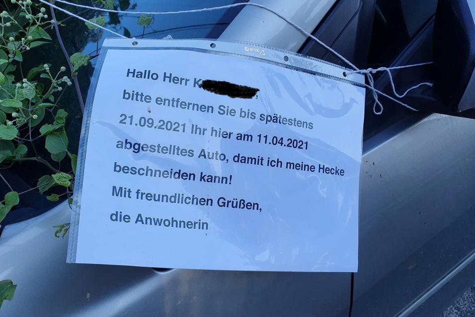 Mit einem angebundenen Zettel fordert die Anwohnerin den Autofahrer zum Wegfahren auf.