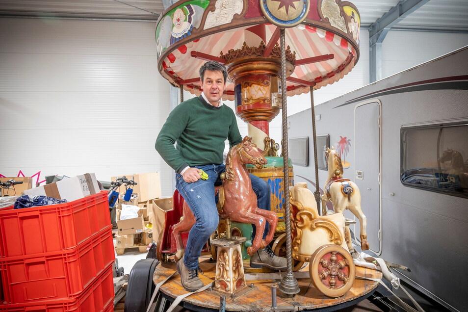 Torsten Pilz mit dem historischen Kinderkarussell, dessen Mittelteil von Künstler Sebastian Bieler auf Vordermann gebracht wird.