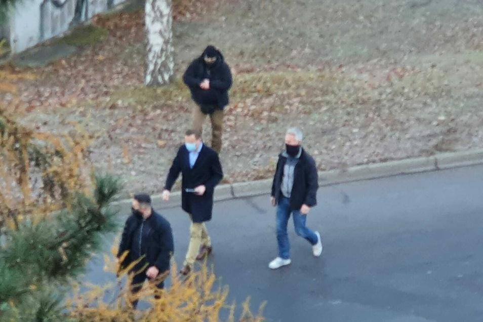 Mit einem Tablet in der Hand und Leibwächtern um ihn herum, geht Nawalny (Mitte) um den Block.