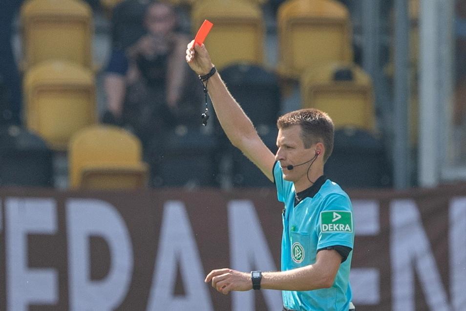 Schiedsrichter Benjamin Cortus zeigt die Rote Karte. Ob das heute Abend auch nötig sein wird? Er pfeift das Ost-Duell von Dynamo bei Hansa Rostock.
