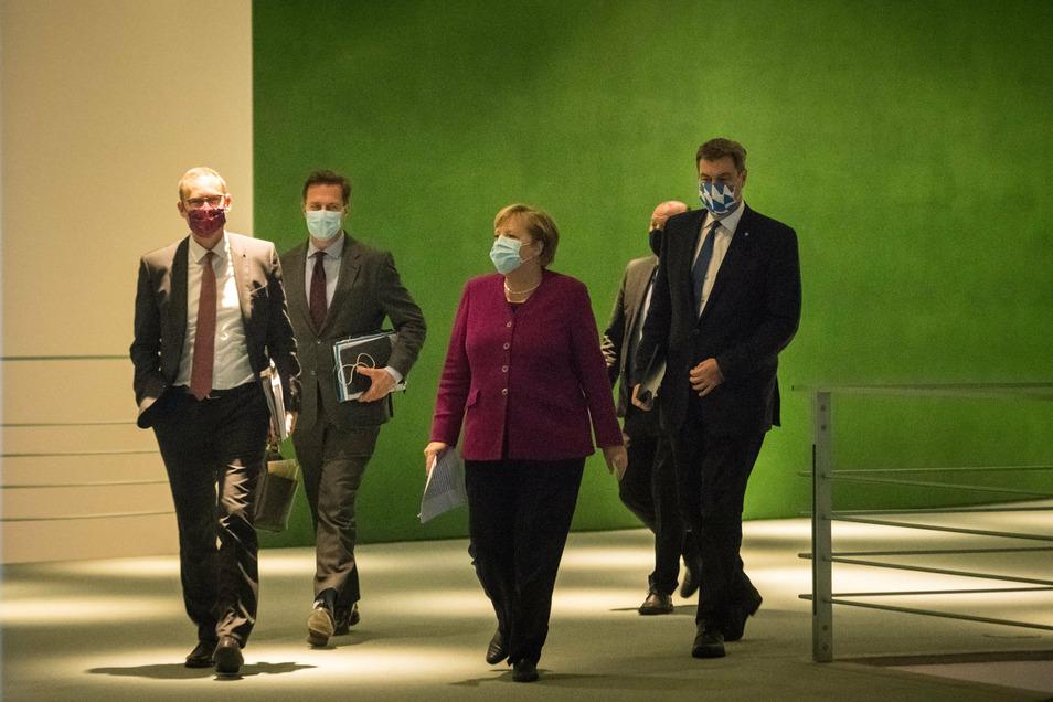 Bundeskanzlerin Angela Merkel kommt mit Markus Söder (r, CSU) und Michael Müller (l, SPD) nach dem Treffen mit den Ministerpräsidenten der Länder zu einer Pressekonferenz.