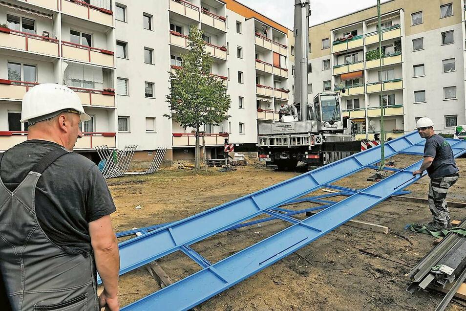 Die Elemente werden durch eine Luke im Dach in den Fahrstuhlschacht eingelassen. Kai Fiedler und Dirk Schmidt von der Alko Fördertechnik GmbH bereiten sie vor.