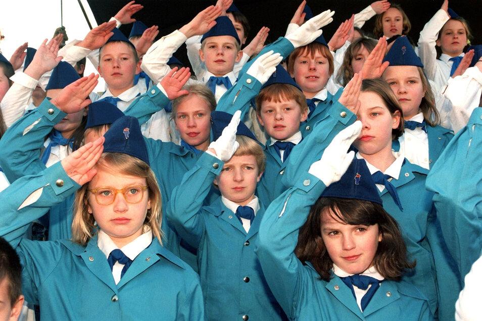 """Gewagte These: Schleppen Kinder der DDR Traumata mit sich rum, weil sie Halstücher trugen und zum Fahnenappell antreten mussten? Wuchsen sie zu Eltern heran, die ihrem Nachwuchs nur selten beistanden? Die Kinder auf dem Foto sind Statisten im Film """"Helden"""