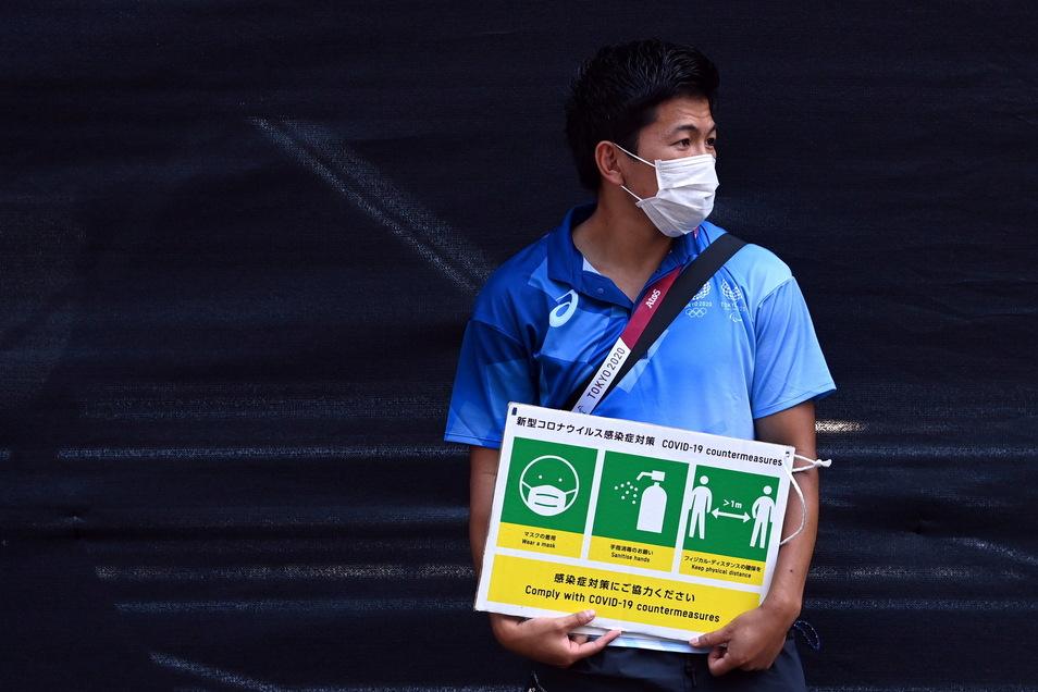 Ein Olympia-Helfer hält ein Schild, das zum Einhalten der Corona-Regeln auffordert.