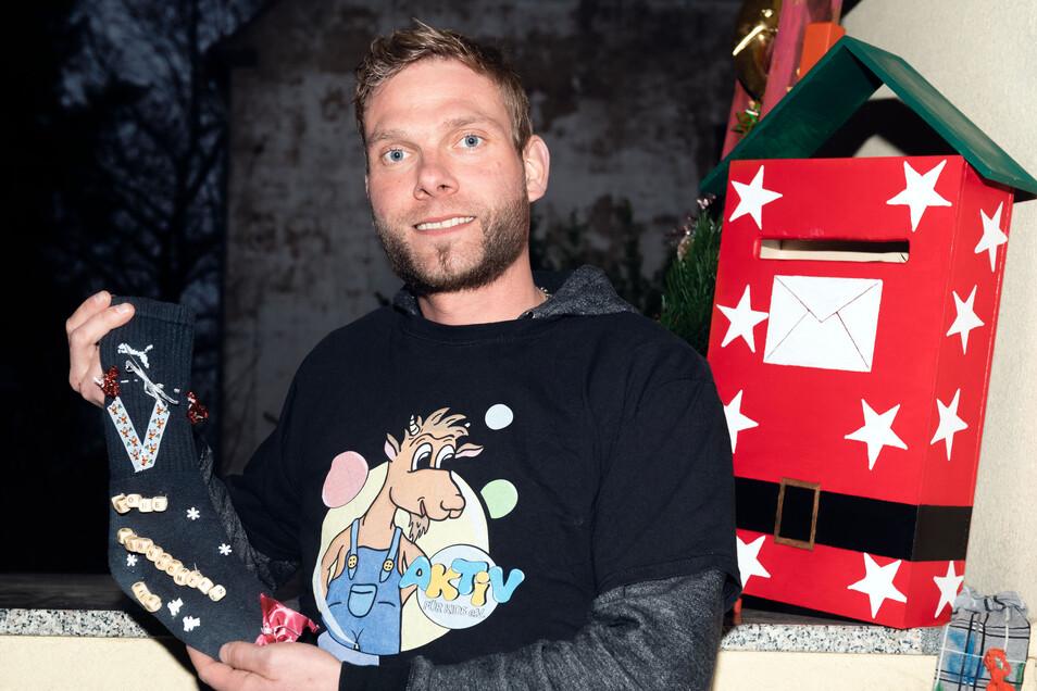 Vereinsvorsitzender René Schmidt zeigt eine verzierte Socke. Die wird für Kinder gefüllt. Vorausgesetzt, man wirft den Strumpf bis zum dritten Advent in den Weihnachtsbriefkasten, der hinter René Schmidt zu sehen ist.