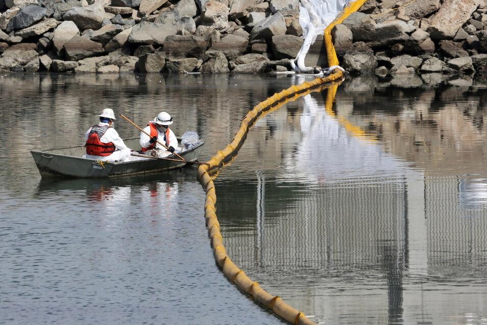Arbeiter sammeln Öl aus dem Meerwasser am Huntington Beach. Über vier Kilometer wurden Ölsperren verlegt.