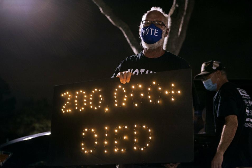 Demonstrant Mark Beaumont nimmt an einer Mahnwache in der Nähe des Trump International Golf Club teil. In den USA sind inzwischen fast 200.000 Menschen nach einer Infektion mit dem Coronavirus gestorben.