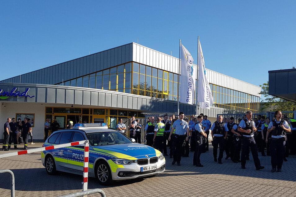 Polizisten stehen am späten Nachmittag vor dem Rheinbad, wo es zu einem Streit mit mehreren Hundert beteiligten Badegästen gekommen ist.