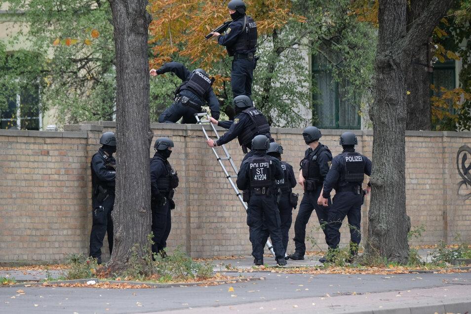 Polizisten überwinden eine Mauer an der Hallenser Synagoge.