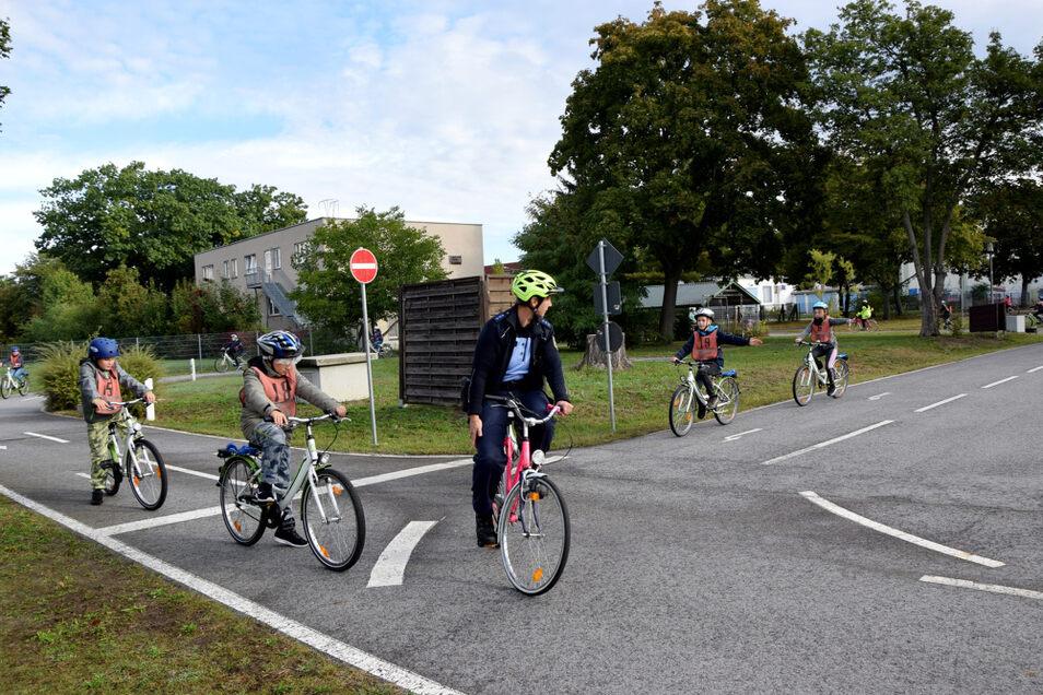 Schüler lernen unter Anleitung, welche Regeln im Straßenverkehr beachtet werden müssen. Das praktische Radfahren im Verkehrspark wird durch eine schriftliche Arbeit ergänzt.