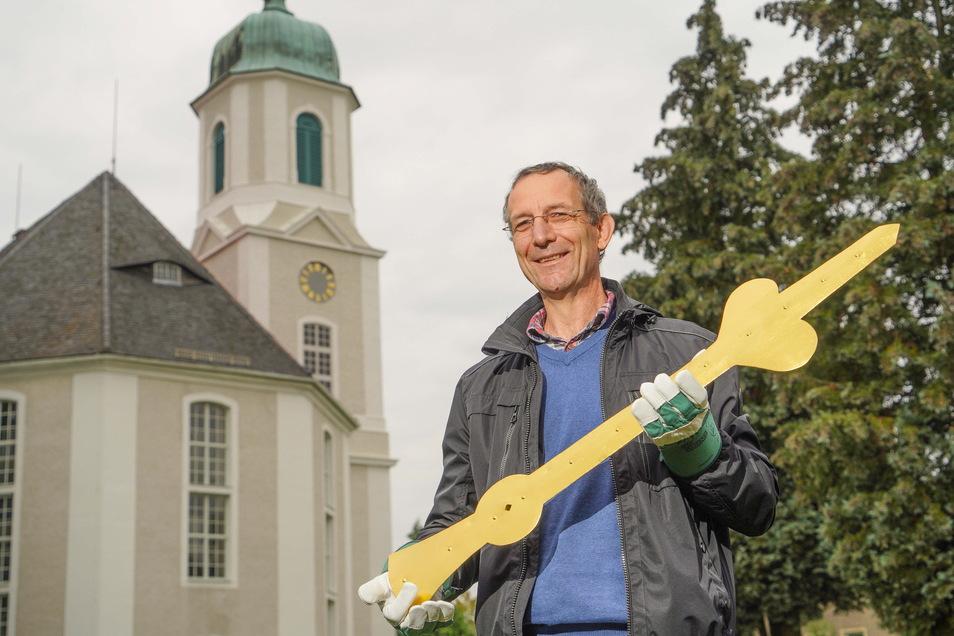 Marko Mitzscherling, Pfarrer der Kirchgemeinde Uhyst a.T., hält hier den Minutenzeiger der Turmuhr noch in der Hand. Inzwischen wurde er montiert.