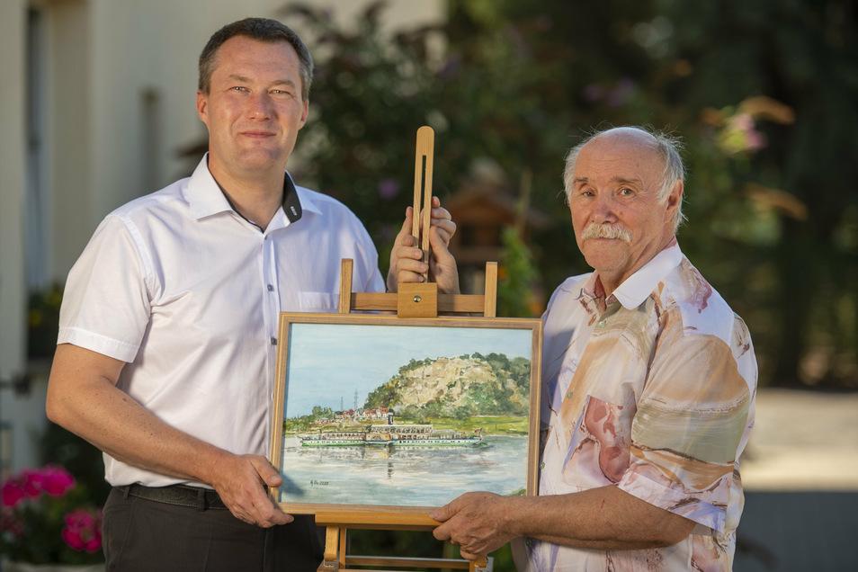 Heimatmaler Hans Obenaus (rechts) aus Weinböhla übergibt Michael Hillmann vom Förderverein aus Dresden sein Bild zur Versteigerung. Mit dem Geld soll der Erhalt der Dampferflotte für Sachsen mit unterstützt werden.