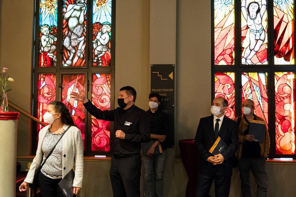 Standortleiter Stefan Kretschmer führt Oberbürgermeister Octavian Ursu und Vertreter der beteiligten Firmen durch den sanierten Filmpalast. Im Hintergrund die beiden wiederentdeckten expressionistisch gestalteten Fenster.
