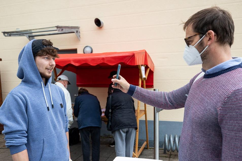 Bastian Schäfer (links) kontrolliert, ob die Gaste - hier André Berndt - geimpft, genesen oder getestet sind. Wer diese Bedingungen erfüllt, darf aufs Festgelände.