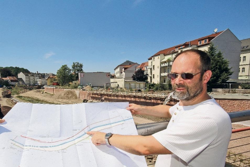 Thomas Zechendorf von der Landestalsperrenverwaltung erklärt auf einem Plan den Baufortschritt der Flutmulde zwischen der Straße des Friedens und der Johannisstraße.