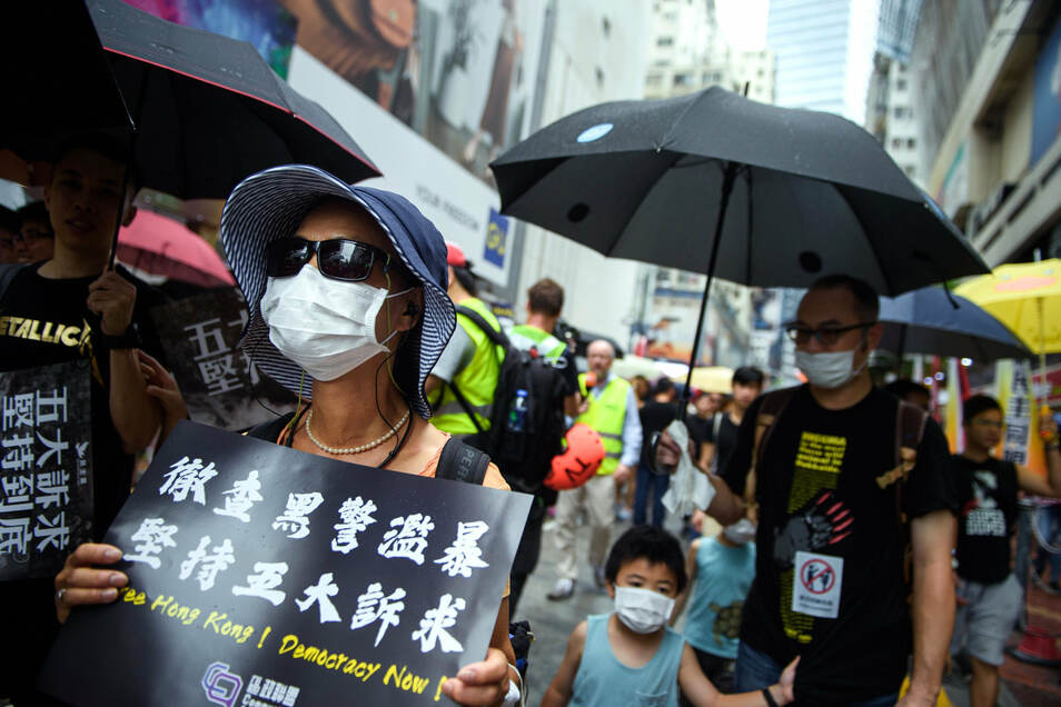 Eine Frau geht mit Mundschutz zur Protestkundgebung im Victoria Park.