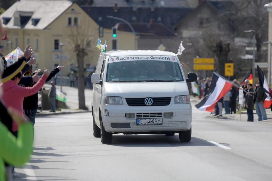 """Kritiker der Corona-Maßnahmen grüßen den Fahrer eines VW Busses, der mit der Aufschrift """"Sachsen zeigt Gesicht"""" auf der B96 durch Oppach fährt."""