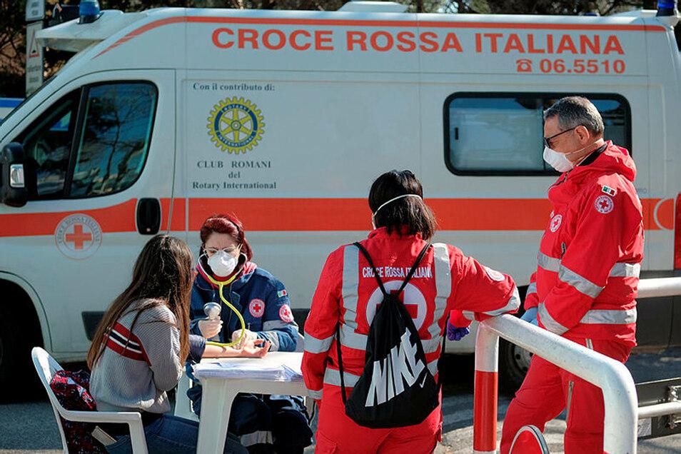 Eine Frau nimmt in der Corona-Krise an einer Blutspende-Aktion des italienischen Roten Kreuzes teil und wird von einer medizinischen Fachkraft mit Mundschutz untersucht.