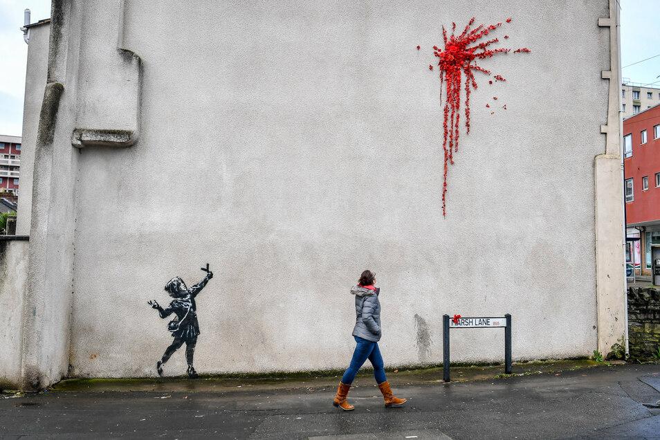 Das neue Banksy-Werk in Bristol: Zu sehen ist ein Mädchen, das mit einer Steinschleuder in der Hand Richtung eines riesigen Kleckses aus roten Rosen zielt.