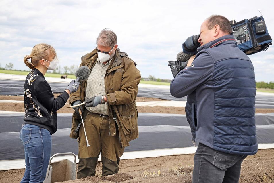 Wie funktioniert das mit dem Spargelstechen? Ein MDR-Drehteam mit Reporterin Susann Schädlich (l.) wollte das am Freitag von Landwirt Hartwig Kübler wissen.