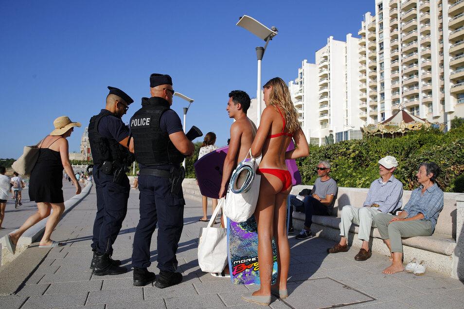 Touristen fragen französische Polizisten auf der Strandpromenade, ob sie am Freitag in Biarritz, surfen können.