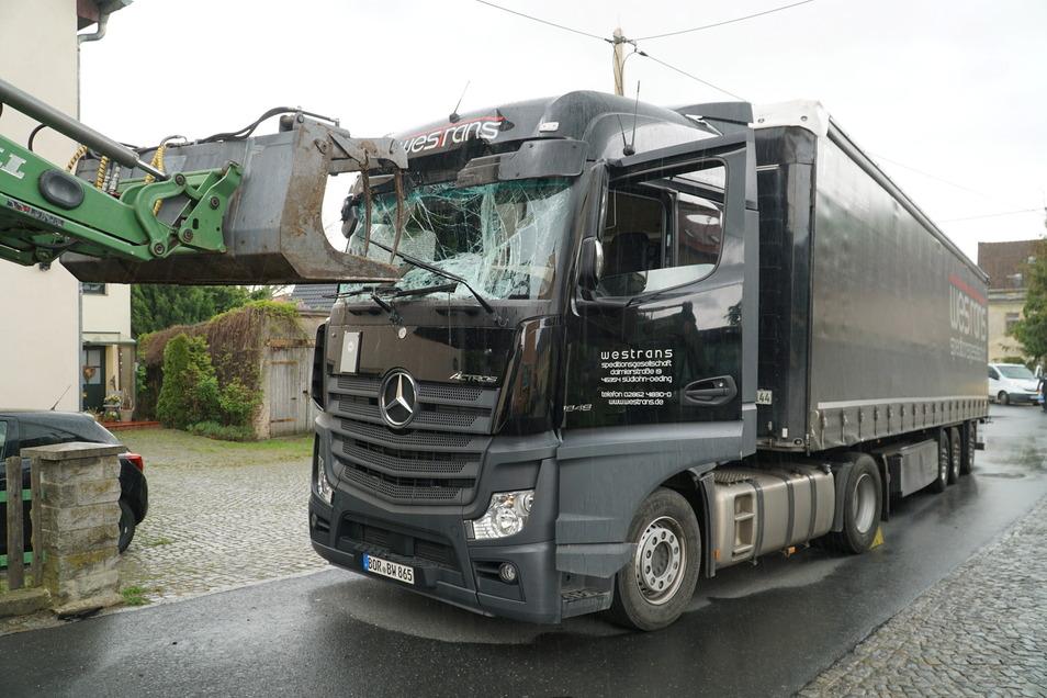 Der Traktor hat mit seiner Schaufel das Fahrerhaus des Lkw eingedrückt. Glücklicherweise wurde niemand verletzt.