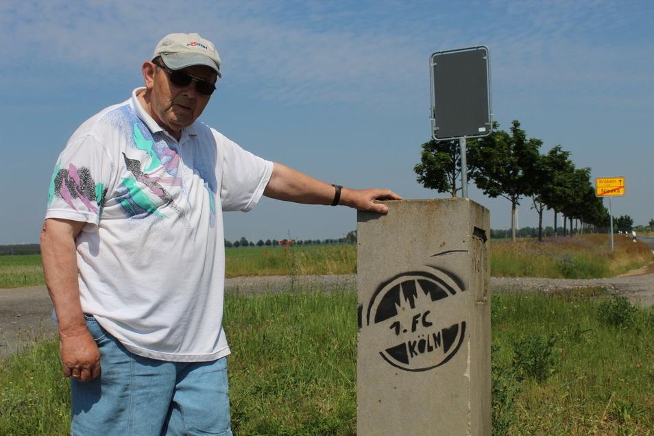 Siegfried Vetter zeigt den besprühten Grenzstein in Nieska, der für Sachsen von historischer Bedeutung ist.
