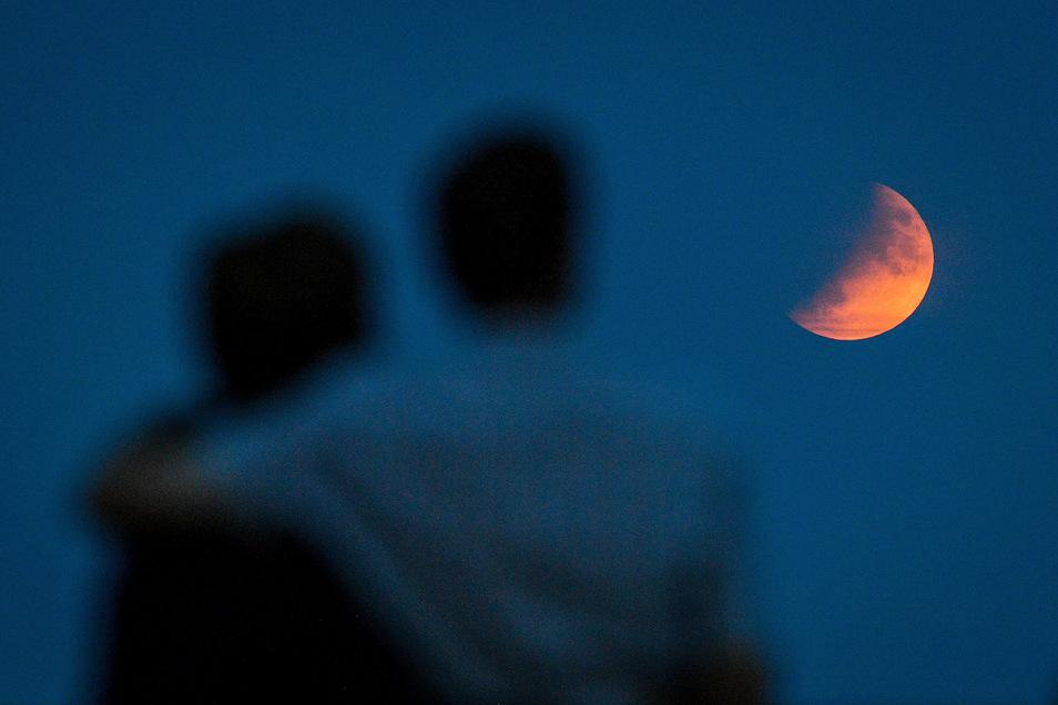Ein Paar beobachtet eine partielle Mondfinsternis inSidmouth.