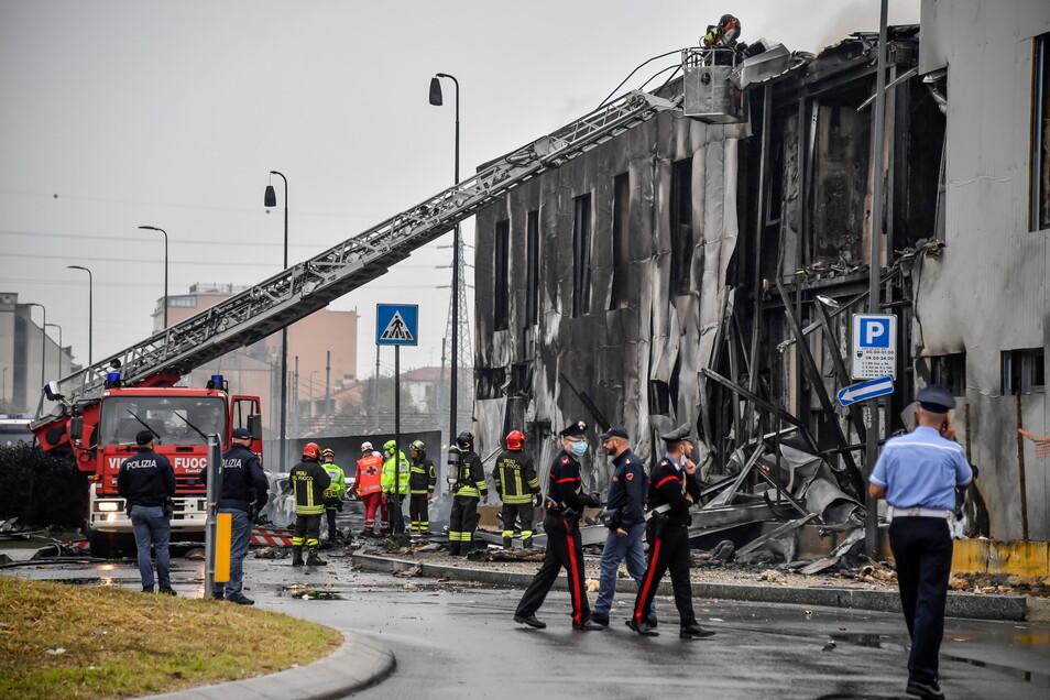 Feuerwehrleute stehen an der Unfallstelle in Mailand, nachdem ein Leichtflugzeug kurz nach dem Start abgestützt und in ein leerstehendes Bürogebäude gekracht ist.